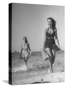 Smiling Girls Carrying Skis Out of the Water onto Beach