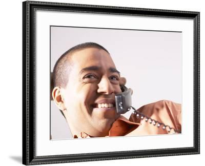 Smiling Man Talking on Telephone--Framed Photographic Print