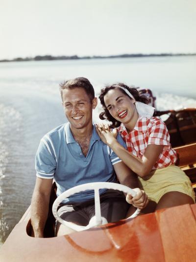 Smiling Retro Couple Enjoying a Speed Boat Ride-Dennis Hallinan-Photographic Print