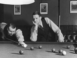 Snooker Player Prepares to Play a Shot as His Partner Looks On
