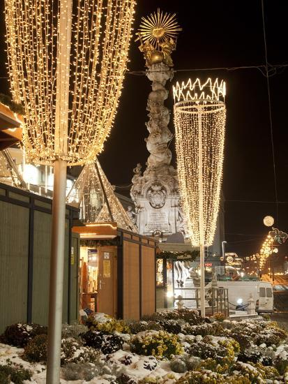 Snow-Covered Flowers, Christmas Decorations and Baroque Trinity Column at Christmas Market, Austria-Richard Nebesky-Photographic Print