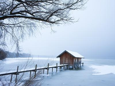 Snow covered pier and boat house at Lake Starnberg-Frank Lukasseck-Photographic Print