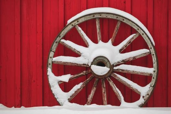 Snow-covered wagon wheels against red barn near town of Banff, Canadian Rockies, Alberta, Canada-Stuart Westmorland-Photographic Print