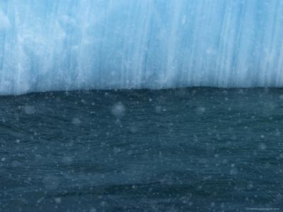 Snow Flakes Drifting Past a Blue Iceberg-Ralph Lee Hopkins-Photographic Print