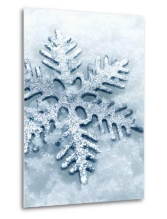Snowflake Shaped Christmas Ornament Lying in the Snow