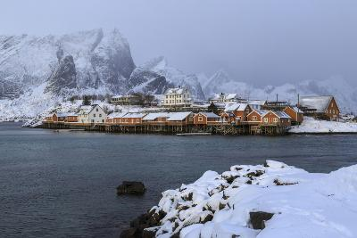 Snowy Peaks and Rorbu, the Red Houses of Fishermen, in the Landscape of the Lofoten Islands-Roberto Moiola-Photographic Print