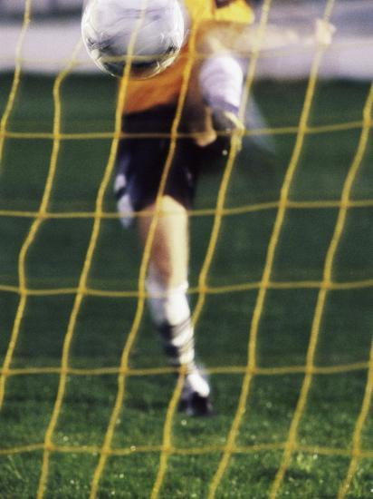 Soccer Player Kicking a Soccer Ball--Photographic Print
