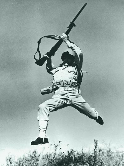Soldier Jumping With Rifle, Low Angle View--Photographic Print
