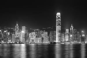 Hong Kong City Skyline at Night over Victoria Harbor with Clear Sky and Urban Skyscrapers. by Songquan Deng