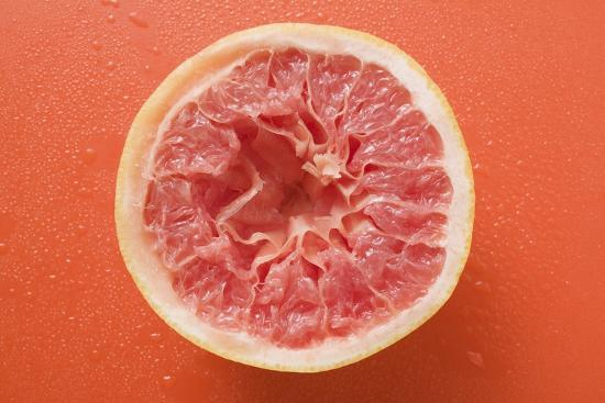 Squeezed Pink Grapefruit on Orange Background-Foodcollection-Photographic Print
