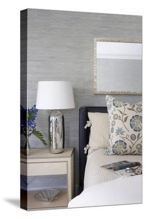 Bed with Chrome Lamp and Floral Cushion