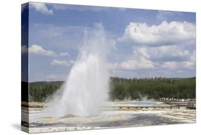 A Geyser Erupts While Tourists Watch from a Boardwalk