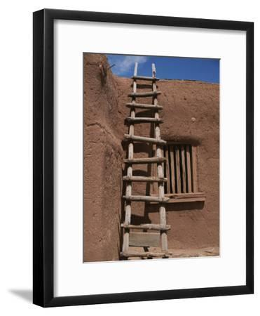 A Handmade Wooden Ladder Rests against an Adobe Structure