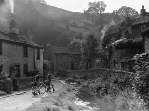 Two boys out on their bicycles near a stream in the Peak District by Staff