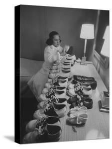 Mrs. Ottilie King Lining Up Her Children's Shoes by Stan Wayman