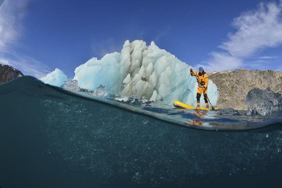 Stand Up Paddle Boarding by an Iceberg, in a Fjord in Southeast Greenland-Keith Ladzinski-Photographic Print