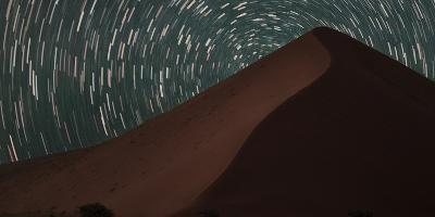 Star Trails Streak across the Sky Behind a Towering Sand Dune in the Namib Desert-Matthew Hood-Photographic Print