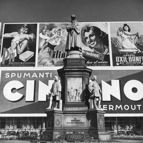 Statue of Leonardo Da Vinci on Top of Monument in Front of Giant Advertising Billboard-Alfred Eisenstaedt-Photographic Print