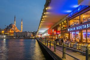 Outdoor Restaurants under Galata Bridge with Yeni Cami or New Mosque at Dusk, Istanbul by Stefano Politi Markovina