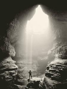 A Man Stands in Front of a Skylit Cave Waterfall by Stephen Alvarez