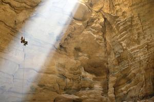 Ben Caddell descends Majlis al Jinn cave. by Stephen Alvarez
