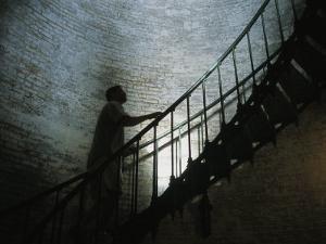 Man Climbs the Staircase Inside the Currituck Beach Lighthouse by Stephen Alvarez