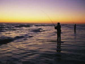 People are Surf Fishing for Red Drum on the Outer Banks of North Carolina by Stephen Alvarez