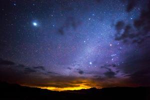 Stars and the night lights of Reno seen from Winnemucca Lake, Nevada. by Stephen Alvarez