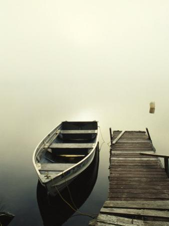 The Morning Sun Shines on a Rowboat Tied to a Dock