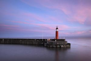 The Lighthouse at Watchet, Somerset, at High Tide under a Colourful Dawn Sky by Stephen Spraggon