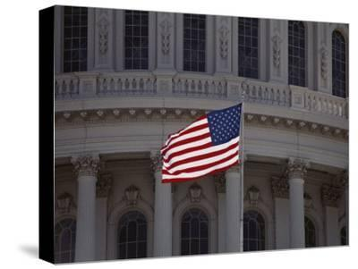 A Backlit American Flag Glows against the Dome of the Capitol Building