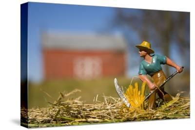 A Lead Figurine of a Farmer Cutting Hay with a Real Barn in Distance