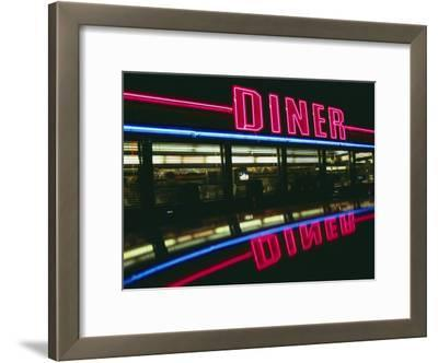 A Neon Diner Sign Relects off a Car Roof