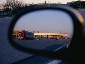 A Rearview Mirror Reflects a Busy Tollgate on the New Jersey Turnpike by Stephen St. John