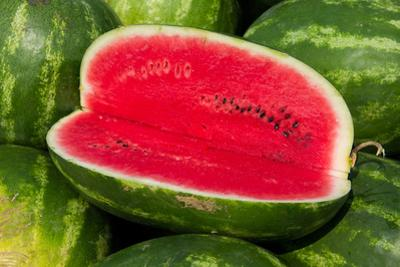 A Sliced-Open Watermelon Reveals the Bright Red Interior by Stephen St^ John