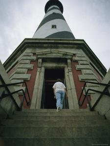 A Woman Enters the Towering Cape Hatteras Lighthouse by Stephen St. John
