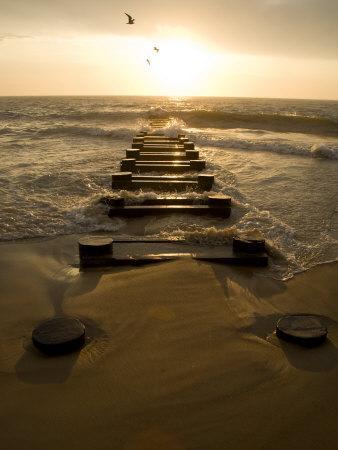 Atlantic Ocean Waves Break Against Pilings at Sunrise