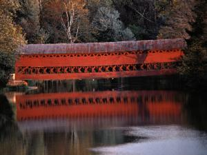 Morning Light Reflects a Red Covered Bridge in River by Stephen St. John