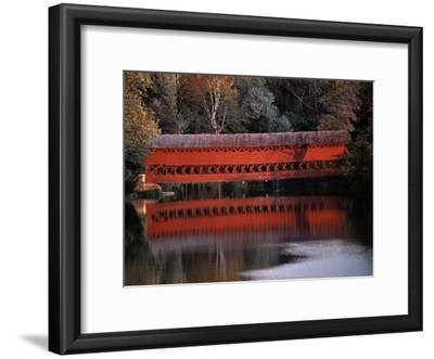 Morning Light Reflects a Red Covered Bridge in River