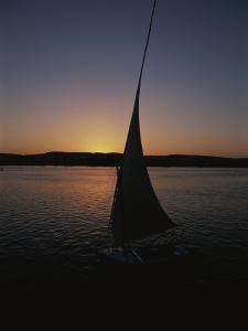 Sunset Outlines the Curve of a Felucca Sail on the Nile River by Stephen St. John