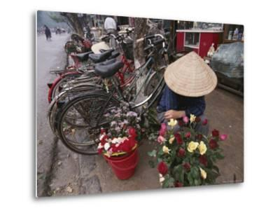 A Flower Vendor Sitting on a Sidewalk Next to a Row of Parked Bicycles