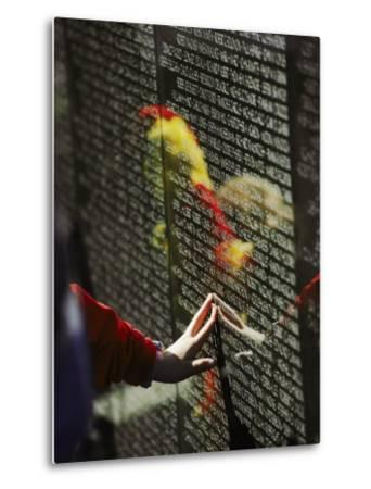 A Hand Reaches out to Touch a Name on the Vietnam Wall