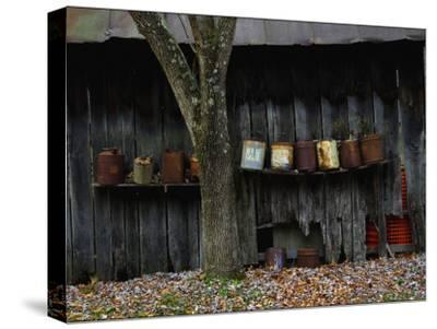 Old Rusted Cans Lined Up on a Shelf on the Side of a Barn