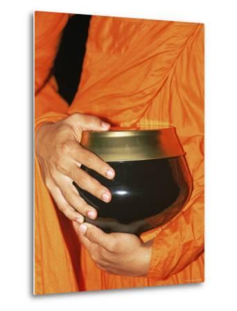 Thailand, Bangkok, Detail of Monk Holding Alms Bowl
