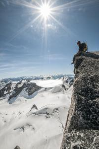 A Young Male Climber on the Summit of Pigeon Spire, Bugaboos, British Columbia by Steven Gnam