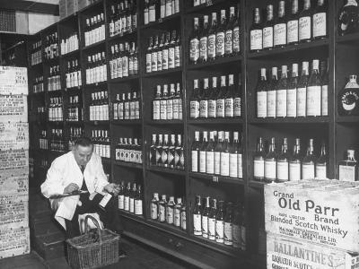 Steward at the Waldorf Astoria Hotel Working in Room Containing Wine and Spirits--Photographic Print
