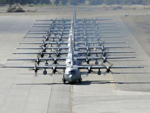 A Line of C-130 Hercules Taxi at Nellis Air Force Base, Nevada by Stocktrek Images
