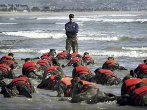 A Navy SEAL Instructor Assists Students During a Hell Week Surf Drill Evolution by Stocktrek Images