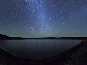 A Panoramic View of the Milky Way and La Azul Lagoon in Somuncura, Argentina by Stocktrek Images