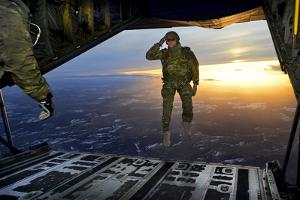 A U.S. Soldier Salutes His Fellow Soldiers While Jumping Out of a C-130 Hercules by Stocktrek Images